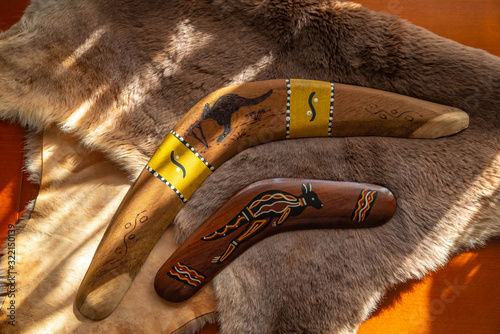 Photo Two old boomerangs laying on the kangaroo skin, fur with wooden glossy table in the background