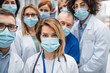 canvas print picture - Group of doctors with face masks looking at camera, corona virus concept.
