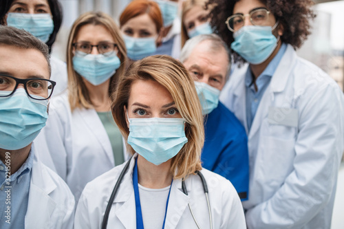 Fotografiet Group of doctors with face masks looking at camera, corona virus concept