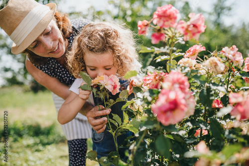 Photo Small girl with senior grandmother smelling roses in the backyard garden
