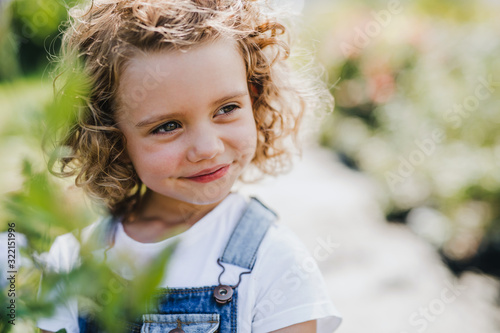 Portrait of small girl standing in the backyard garden. Fototapet