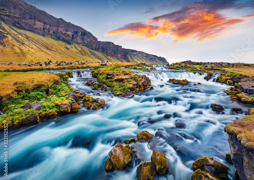 Romantic summer view of small waterfall near Bjodvegur road. Impressive sunrise on Iceland, Vik location. Beauty of nature concept background. - 322152552
