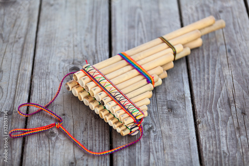 Pan flute (panpipes or syrinx) a musical instrument lying on square-edged floori Fototapet
