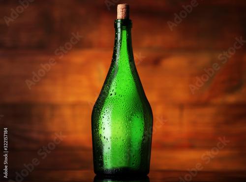 Photo empty green mead bottle in drops