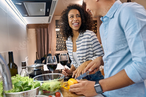 Fototapeta Young adult wife and husband smiling, cooking dinner on kitchen obraz