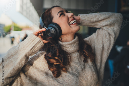 Obraz na płótnie Young happy woman listening to music in headphones outdoors, positive hipster gi