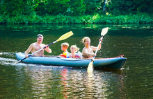 A Young Family With A Son And Daughter Are Kayaking On The Lake .