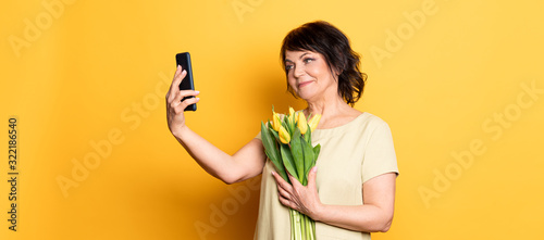 Photographie Beautiful old woman with professional smokey make-up and hairstyle holding tulip flowers on the pink background