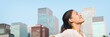 Leinwanddruck Bild - Happy healthy woman taking deep breath in city clean air for pollution concept panoramic lansdcape header banner. Asian lady in Asia face portrait with closed eyes.