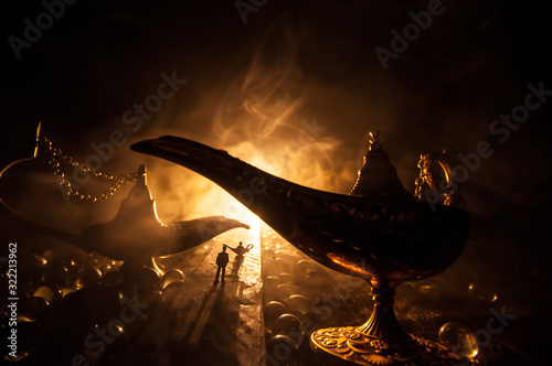 Photo Silhouette of a man standing in the middle of the road on a misty night with giant Antique Aladdin arabian nights genie style oil lamp