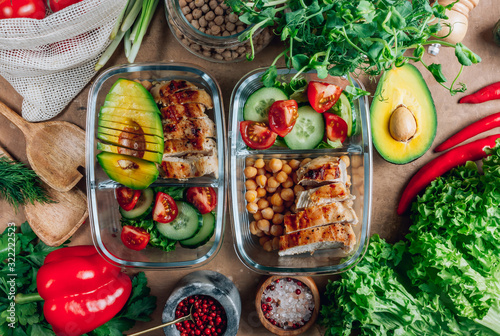 Fototapeta Healthy meal prep containers with chickpeas, chicken, tomatoes, cucumbers and avocados. Healthy lunch in glass containers on beige rustic background. Zero waste concept. Selective focus. obraz