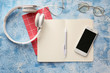 canvas print picture Notebooks with mobile phone, headphones and eyeglasses on color background