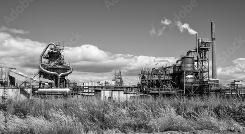 Fényképezés Greyscale of a factory surrounded by the grass under the sunlight and a cloudy s
