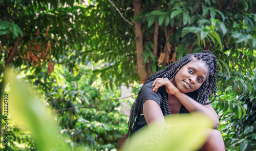 Charming beautiful young african american woman girl with black pigtails with piercings on her face, portrait in a tropical garden