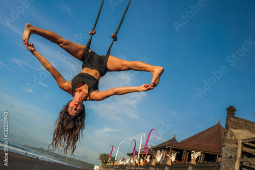 aero yoga beach workout - young attractive and athletic woman practicing aerial Wallpaper Mural