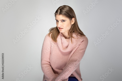Fotografija Close up portrait of a young Caucasian woman wearing a pink sweater on a grey background