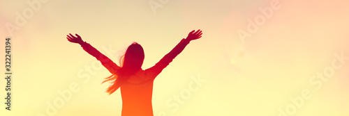 Happy woman sihouette with arms raised up in success on sunset glow sunshine banner panorama Fototapete