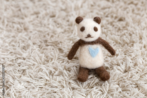 handmade felt panda bear on white carpet