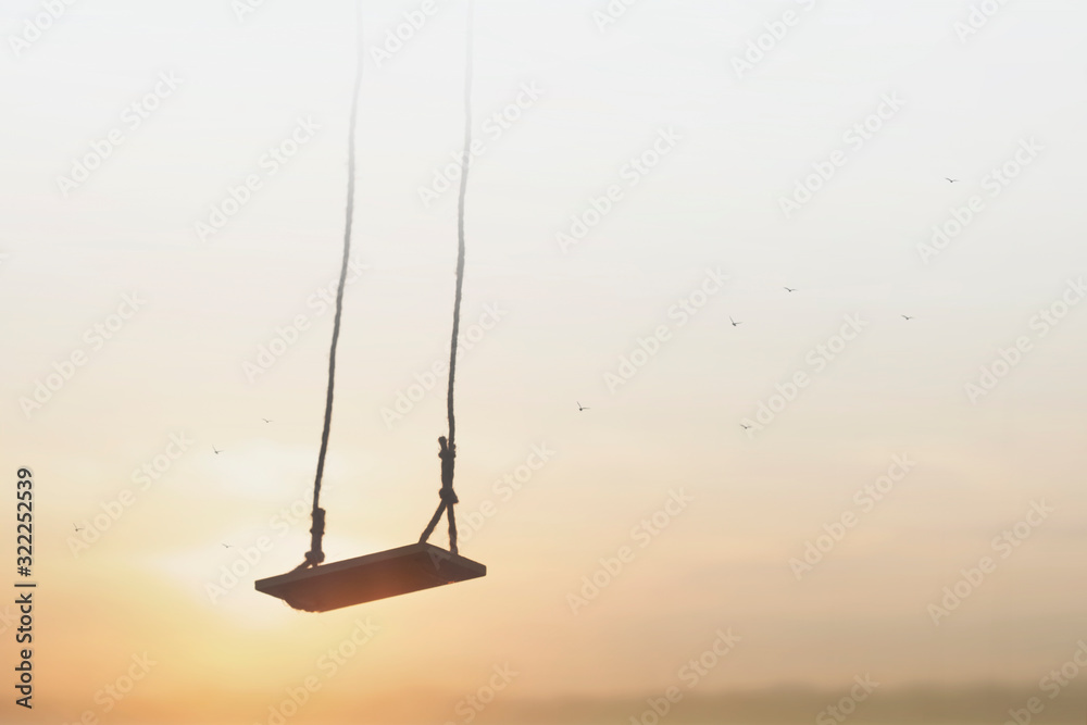 Fototapeta lonely swing surreally hanging from the sky