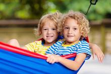 Boy In Hammock. Kids Play In Summer Garden.