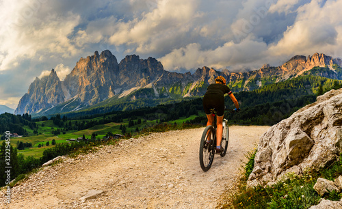 mata magnetyczna Tourist cycling in Cortina d'Ampezzo, stunning rocky mountains on the background. Woman riding MTB enduro flow trail. South Tyrol province of Italy, Dolomites.