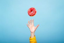 Hand Catch A Donut With Red Icing. Blue Cardboard Background. The Concept Of Baking, Handmade. Flat Lay, Top View