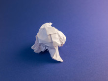 Crumpled White Paper On A Blue...