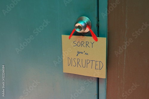 Fotografie, Obraz Closeup handwriting cardboard sign with message read sorry you are disrupted han