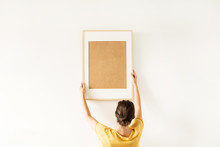 Young Pretty Woman Hold Blank Photo Frame With Empty Mockup Copy Space. Minimal Art Concept.