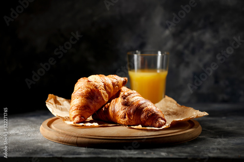 Dark mood background and fresh croissants on board Fototapeta