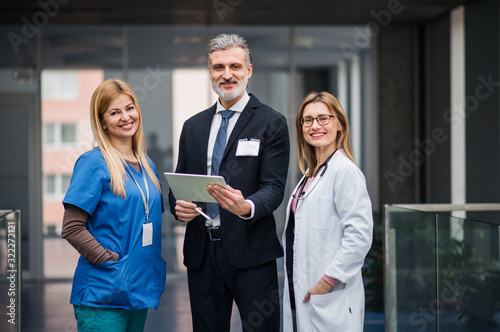 Doctors with pharmaceutical manager standing in corridor.