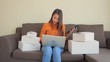Boxes surround a young woman with a tablet in one hand and a laptop on her legs inputs data and dramatically with a fist pump when finished typing.
