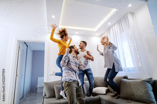 Obraz Group of cheerful best friends having fun at home. They are jumping on sofa and laughing. - fototapety do salonu