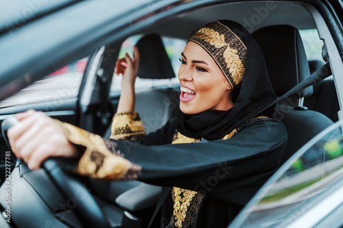 Obraz na plátně Cheerful gorgeous positive muslim woman in traditional wear driving her new car, listening music and singing