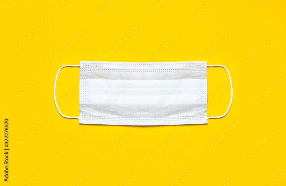 Fototapeta Medical mask on yellow background flat lay top view with copy space. Protection against virus, coronavirus, flu, colds, diseases. Traditional medical tool, concept of health. Medical background