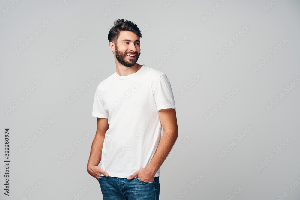 Fototapeta Handsome young man smiling isolated on grey background wearing casual t-shirt and jeans looking away