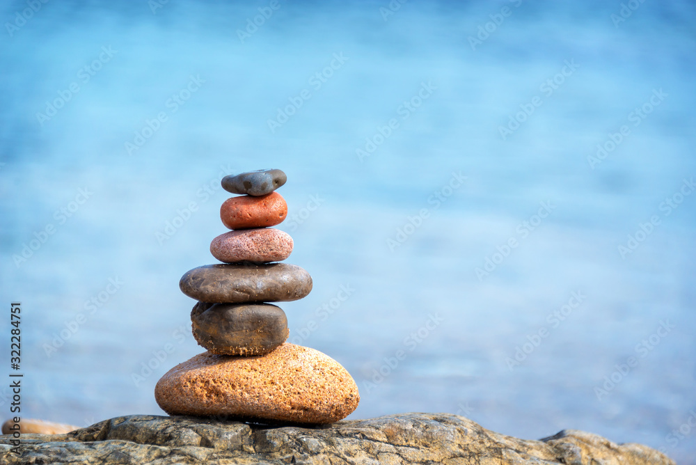 Fototapeta Pile of pebbles on a beach, blue water background