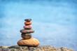 Leinwandbild Motiv Pile of pebbles on a beach, blue water background