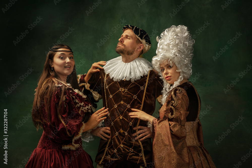 Fototapeta Love games pay attention. Portrait of medieval young people in vintage clothing on dark background. Models as a duke and duchess, princess, royal persons. Concept of comparison of eras, modern