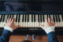 A Male Musician Plays The Piano, Presses Hands And Fingers On Black And White Keys Close-up. Photography, Concept.