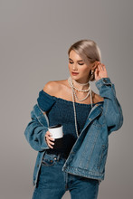 Attractive Woman In Denim Jacket And Jeans Holding Insulated Mug Isolated On Grey