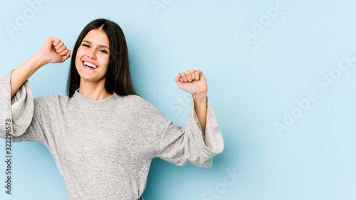 Fotografia Young caucasian woman isolated on blue background dancing and having fun