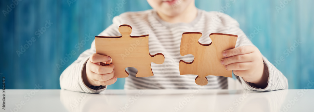 Fototapeta Little child holding puzzle pieces and trying to solve it