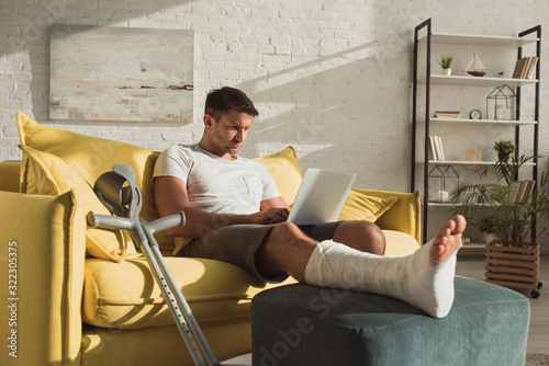 Valokuva Handsome man with broken leg using laptop near crutches on sofa