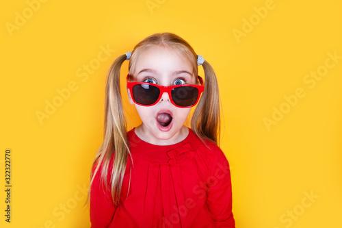 Obraz Shocked little girl in red sunglasses over yellow background - fototapety do salonu