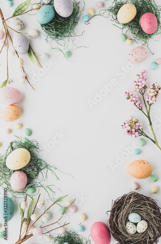 Fototapeta Top down view of an Easter border flat lay including robin's eggs, chocolate eggs and nests in desaturated colours. obraz