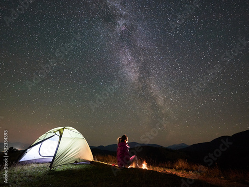 Obraz Female camper having a rest at summer night camping in the mountains beside bonfire, glowing tourist tent. Young woman enjoying view of night sky full of stars and Milky way. Tourism adventure concept - fototapety do salonu