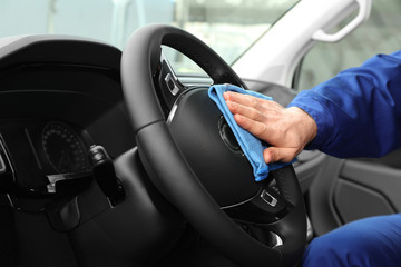Car wash worker cleaning automobile interior, closeup