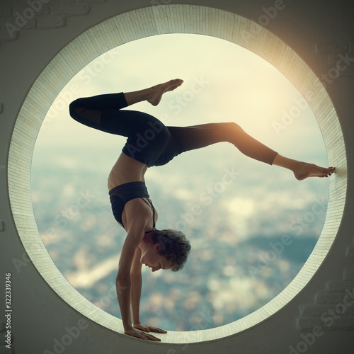 Fotografie, Tablou Beautiful sporty fit yogi woman practices yoga handstand asana Bhuja Vrischikasa