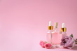 Leinwanddruck Bild Bottles of essential oil and flowers on pink background. Space for text